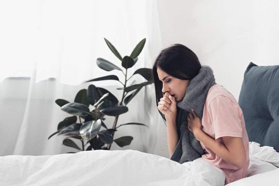 ベッドで咳をする外人女性